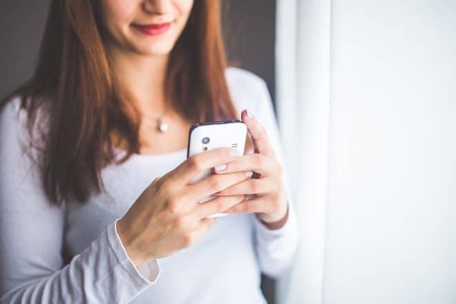 Une jeune femme écrivant un SMS.
